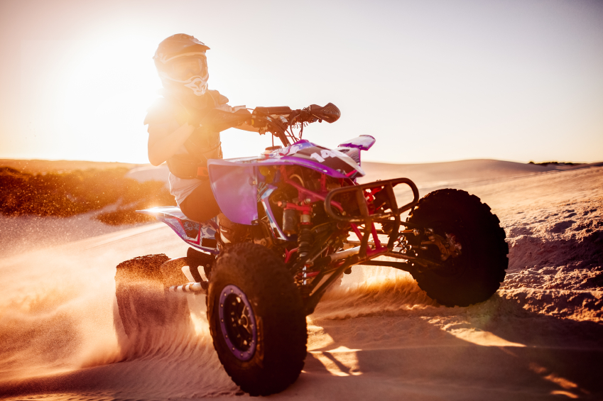 Competitive quad biker with bright sun flare behind driving in a desert race