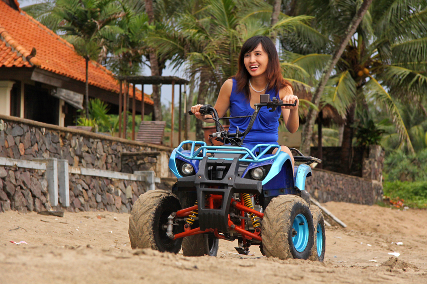 """a young woman riding ATV motor on anyer beach, west java"""